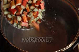 В кипящую воду, добавляем нарезанный ревень и дольки лимона. Убавить огонь, варить около 10 минут.