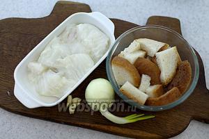 Хлеб нарежьте небольшими кусочками. Залейте тёплой водой. Разморозьте зубатку, отделите филе от косточек. Нарежьте небольшими порциями. Очистите лук и чеснок.
