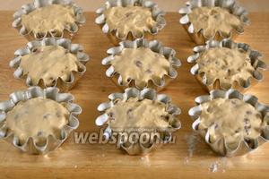 Разложите тесто в формочки, наполняя их на 2/3. Разровняйте поверхность, смоченной в воде ложкой.