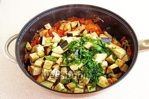 В сковороду к филе выложить баклажаны и измельчённую зелень петрушки.