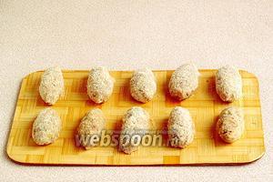 Из фарша сформовать маленькие колбаски и обвалять их в панировочных сухарях.