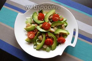 Помидоры черри разрежем пополам, авокадо — на дольки. Выложим всё в тарелку.