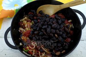 Добавьте варёную чёрную фасоль. Перемешайте. Приправьте солью и молотым перцем. Жарьте около 5 минут.