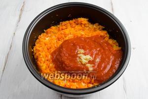 По сигналу открыть крышку мультиварки.  Добавить томат с солью и перцем, рубленый чеснок и оставшееся масло. Перемешать.