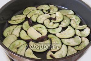 Разогреем сковороду, нальём растительного масла и выложим дольки баклажанов 1 слоем.