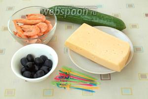 Для приготовления канапе нам понадобятся замороженные креветки, свежий огурец, твёрдый сыр и маслины без косточки. Также нам понадобятся шпажки. Креветки следует разморозить, затем залить кипятком и остудить. Потом почистить.