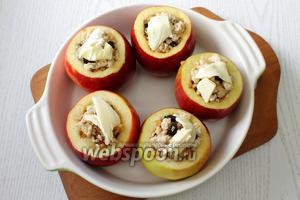 На каждое яблоко выкладываем по 1 кусочку сливочного масла. Вливаем к яблокам бульон и накрываем фольгой или крышкой.