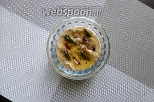 С сыра срежем верхнюю корочку, кладём его в огнеупорную, удобную форму. Делаем сверху несколько надрезов, в которые вставляем по кусочку чеснока, веточки розмарина или чили. Сверху сбрызнем оливковым маслом.