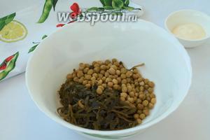 В миску выложить морскую капусту и консервированный горошек. Капусту по желанию можно нарезать на более мелкие полоски.