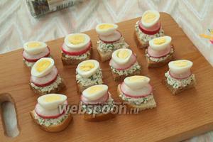 Смесь из брынзы намазать на хлеб, сверху положить по кружочку редиса и половинку перепелиного яйца.