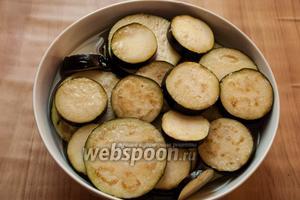 Баклажаны помыть, порезать на кружочки и залить солёной водой на 20 минут, чтобы убрать горечь.