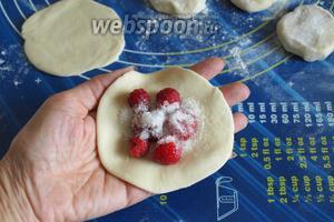 Лепёшку выложить на ладонь, в центр поместить 6-7 ягодок малины. Посыпать малину сахаром по 1 ч. л.