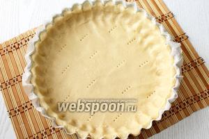 Форму застилаем бумагой для выпечки или смазываем сливочным маслом. Раскатываем тесто и переносим его в форму, подравниваем аккуратно края. Прокалываем в нескольких местах тесто вилкой.