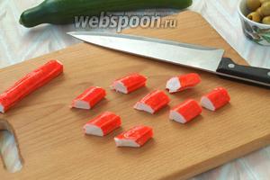 Нарезать крабовые палочки брусочками наискосок.