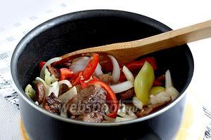 Добавить сладкий и острый перец, а так же лук. Подсолить по вкусу и ещё обжарить все вместе до приемлемой мягкости перца и лука.