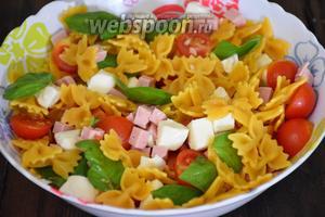 К пасте добавить Моцареллу, кубики ветчины, помидоры с базиликом, посолить по вкусу, добавить оставшееся оливковое масло и перемешать.