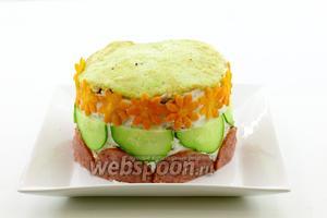 Теперь украсьте боковую стенку по всему кругу. Для этого нарежьте колбасу и огурец тонкими полукольцами. Морковь можете предварительно отварить для украшения или нарезать тонкими полосками и подержать 20-30 секунд в микроволновке. Тогда морковь станет мягче и с ней будет удобно работать. Плунжером вырежьте небольшие цветочки. Украсьте торт, как указано на фото. Приветствуется ваша фантазия. Возможно получится ещё красивее.