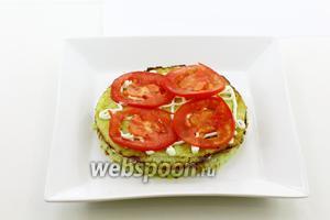 На колбасу уложите следующий кабачковый кружочек. Также сдобрите майонезной сеточкой. Добавьте тонкие кружочки помидора.
