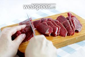 Слегка подмороженную мякоть нарезать тонкими пластинками, а затем поперёк тонкой соломкой. Чем тоньше нарезка, тем быстрее мясо приготовится.