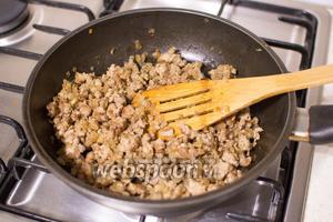 Добавьте фарш, жарьте, пока он не изменит цвет. Снимите с огня, приправьте солью и перцем, немного остудите.