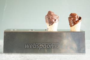 Переворачиваем мороженое вниз головой, окунаем до основания конуса в кружку с растопленным шоколадом, достаём — чудо свершилось, оно опять не выпало!!!