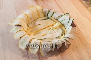 Форму для выпекания смазываем маслом и выкладываем ленты цукини так, чтобы они свисали за борт формы. Немного солим наш цветочек.