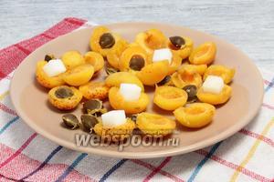 Тем временем чистые, сухие абрикосы разрываем пополам, выбрасываем косточки и на их место укладываем по куску рафинада. Накрываем свободными половинками.