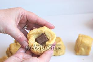 В больший шарик кладём, в середину, кусочек шоколада. Защипываем и швом вниз кладём в форму для маффинов.