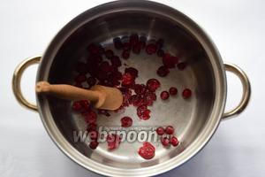 В толстостенной кастрюле разомнём ягоды клюквы! Если ягоды используются замороженные, сначала рекомендуется их немного разморозить!