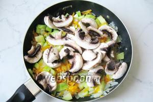 Добавить шампиньоны в сковороду к луку, моркови и кабачкам. Налить подсолнечное масло и 50 мл воды.  Сковороду накрыть крышкой и поставить на огонь. Тушить овощи с грибами 20 минут на среднем огне до готовности, периодически перемешивая.