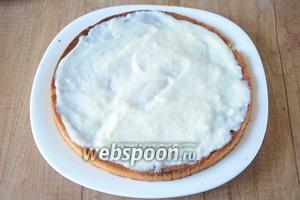 Теперь займёмся сборкой торта. Когда крем остынет, на блюдо выкладываем первый бисквитный корж и хорошо смазываем его остывшим кремом.