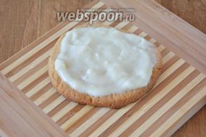 Когда печенье остыло, выкладываем печенье на рабочую поверхность. Десерт будет многоярусным, поэтому каждый слой теста необходимо смазать заварным кремом (кроме верхнего коржа).