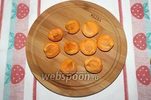 1/2 часть абрикосов порежьте пополам.