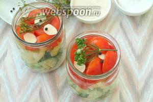 Нарезать дольками помидоры и наполнить банки до верха. Чеснок нарезать пластинками и разложить сверху. Выложить по соцветию укропа в каждую баночку и перец горошком.