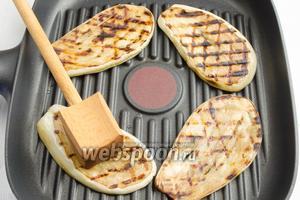 Обжарить дольки баклажана на сковороде-гриль с двух сторон. Остудить.