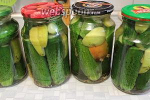 Залить огурцы с яблоками кипятком, прикрыть прокипячёнными крышками, оставить на 3-4 минуты.