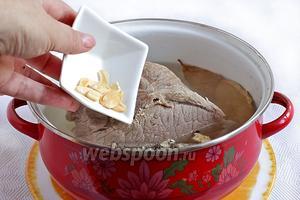 Затем добавить сушёный пластинками чеснок и сухие коренья.
