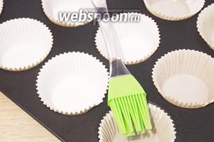 Разогрейте духовку до 180°C. Формочки или бумажные капсулы необходимо смазать маслом при помощи кисточки. Сделать это надо обязательно, так как в рецепте отсутствует масло.
