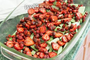 Выкладываем ревень в жаропрочное деко, сверху — целые ягоды лесной земляники и половинки садовой.