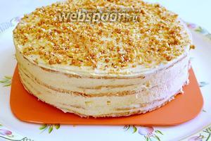 Промазываем наши коржи тонким слоем крема и посыпаем каждый корж измельчёнными карамельными орехами. Бока торта промазываем кремом, выравнивая их. Чтобы коржи сильно не пропитались кремом и не стали мягкими, сразу поставим торт в холодильник на 1-2 часа.