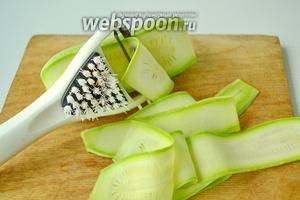 Кабачок стоит предварительно помыть. Нарезаем произвольно. Я решила порезать на тонкие слайсы при помощи овощерезки.