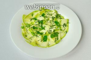Собираем салат. Укладываем слой кабачка, можно скрутить каждую дольку трубочкой, затем посыпать кунжутом, зеленью. И так несколько слоев.