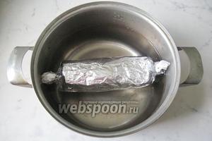 В кастрюлю налить воду, выложить батон будущей колбасы.