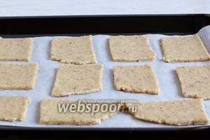 Раскатать тесто в пласт, толщиной 4-5 мм, и разрезать на прямоугольники. Для удобства сразу выложить прямоугольники на противень с пергаментом.