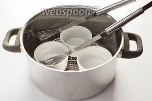 Приготовление сливок с яйцом следует начинать не с описания ингредиентов, а с описания посуды для их приготовления. Для этого блюда нужны какие-то небольшие термостойкие плошечки — может быть, кокотницы, а может рамекины. Нужна большая кастрюля с крышкой или очень глубокий сотейник. Очень желательна решётка, которая помещается на дно кастрюли. Кокотницы будут устанавливаться на эту решётку, чтобы они равномерно прогревались. Счастливые обладатели мультиварок, думаю, могут как-то приспособить для этого рецепта свои приборы, но я, уж простите, прибором не владею, я — по старинке. Ну, и ещё желательны какие-нибудь щипцы или плоская шумовка, или лопатка, которой можно будет помещать и извлекать мисочки из кастрюли. И вот только тогда, когда вы выясните, сколько у вас кокотниц есть, и сколько их влезает в кастрюлю, можно задумываться насчёт количества ингредиентов.