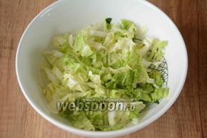 Мелко нашинковать пекинскую капусту, уложить её на дно салатника, посыпав немного солью.