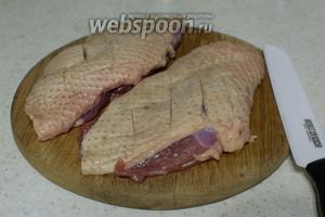 Утиные грудки помойте, просушите полотенцем, сделайте на коже ромбовидные надрезы, стараясь не прорезать мясо. Посолите и поперчите.