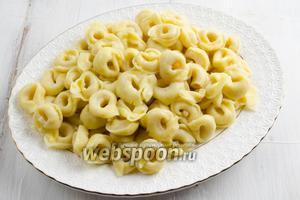 Вернуть тортеллини в кастрюлю. Добавить ложку пряного оливкового масла от вяленых помидоров. Перемешать. Выложить на блюдо.