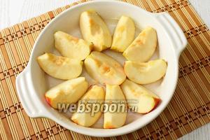 Форму для запекания смазываем маслом, выкладываем дольки и сбрызгиваем яблоки лимонным соком.
