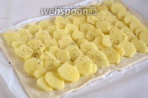Раскатайте слоёное тесто в 2 прямоугольника, размером около 25х35 см. На 1 прямоугольник выложите тонкие кружочки сырого картофеля, посолите и поперчите.